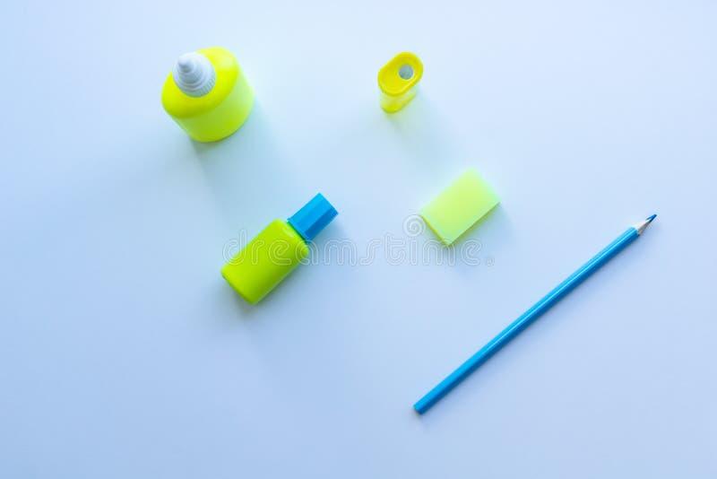 混杂的文具顶视图在黄色和蓝色颜色的:胶浆、磨削器、橡皮擦、铅笔和修正液在白色背景 库存图片