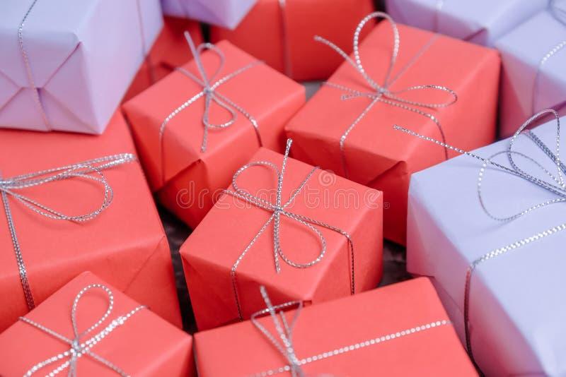 混杂的礼物包裹在红色和淡紫色纸和栓与银 免版税库存图片