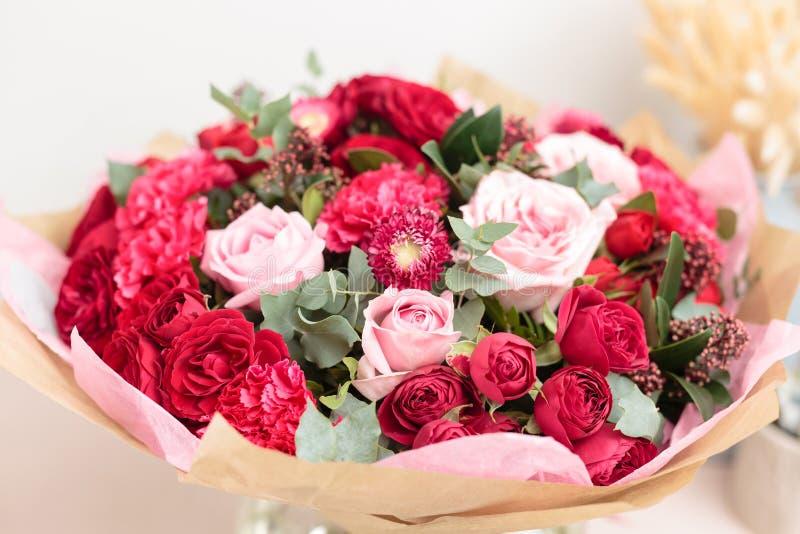 混杂的红色和桃红色花特写镜头美丽的豪华花束在玻璃花瓶的 卖花人的工作在花店 库存图片
