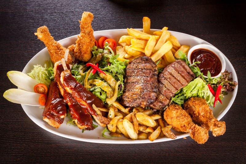 混杂的肉、沙拉和炸薯条盛肉盘 库存照片