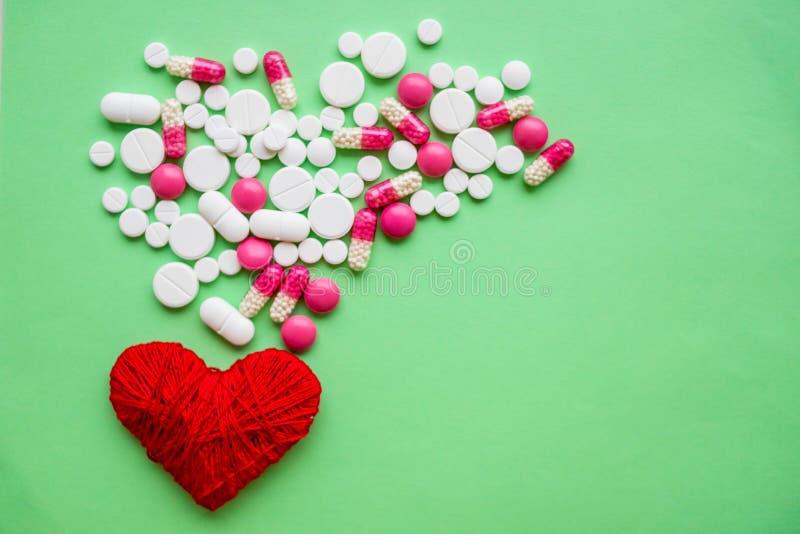 混杂的胶囊和果子在一心形在白色木背景 维生素和补充和医疗保健概念 红心机智 免版税库存图片