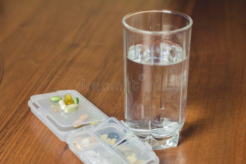 混杂的自然食物补充和维生素药片,杯在木桌上的水 免版税库存照片