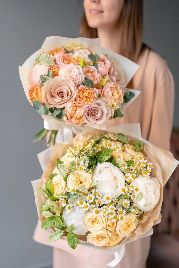 混杂的花两小美丽的花束在妇女手上 花卉商店概念 E 库存照片