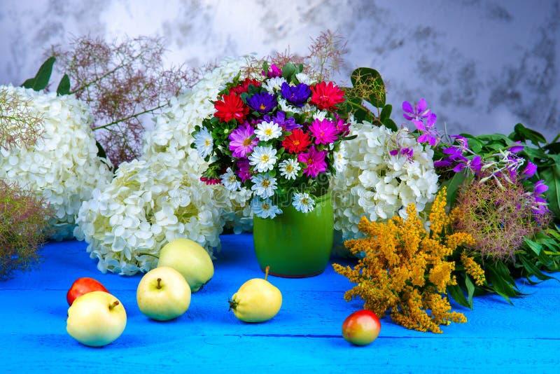 混杂的花和果子在一张木桌上 免版税库存照片