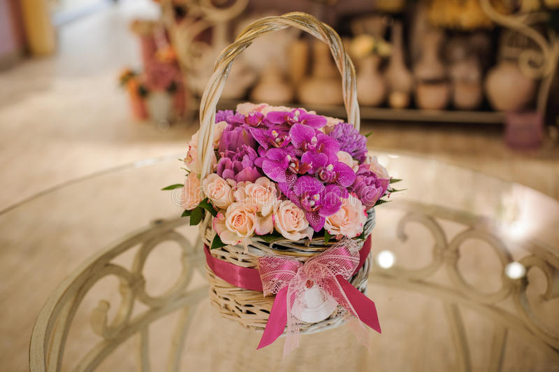 混杂的花美丽的桃红色花束在篮子的在桌上 免版税库存照片