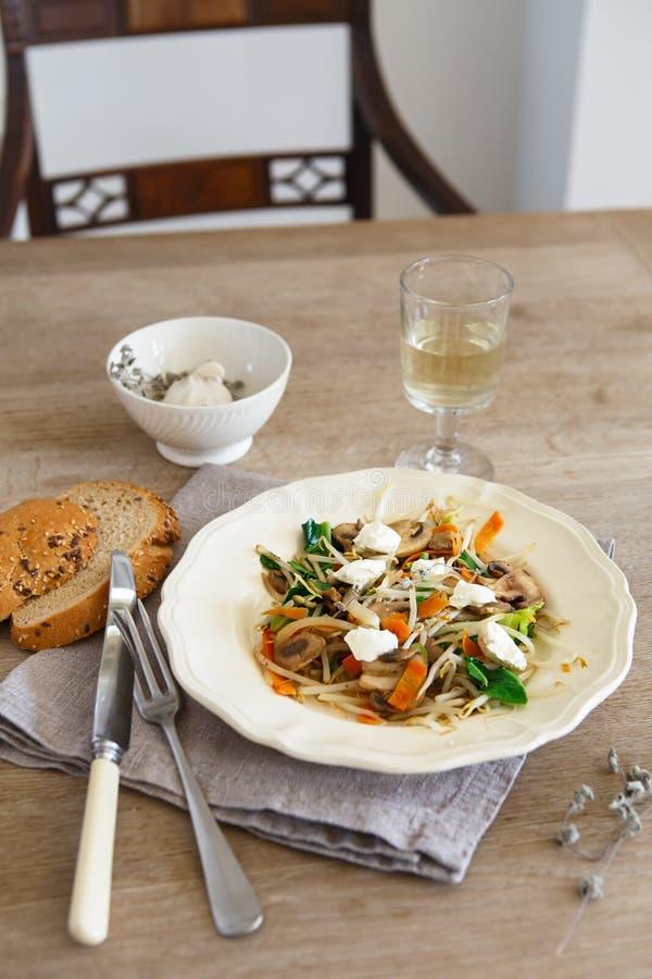 混杂的菜混乱油炸物用蘑菇和村庄奶油奶酪 嫩蘑菇混乱油炸物在有白酒的一块白色板材服务 库存照片