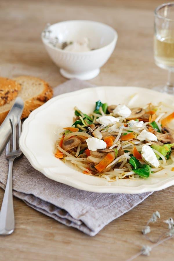 混杂的菜混乱油炸物用蘑菇和村庄奶油奶酪 嫩蘑菇混乱油炸物在有白酒的一块白色板材服务 免版税图库摄影