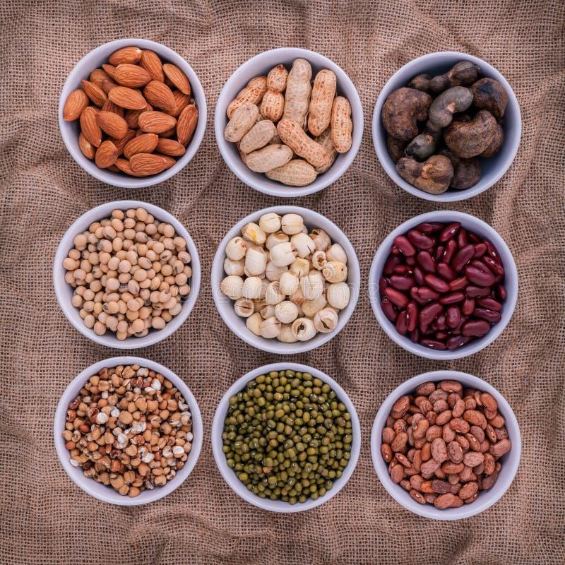 混杂的豆、扁豆和坚果在白色碗在棕色布料 免版税库存照片