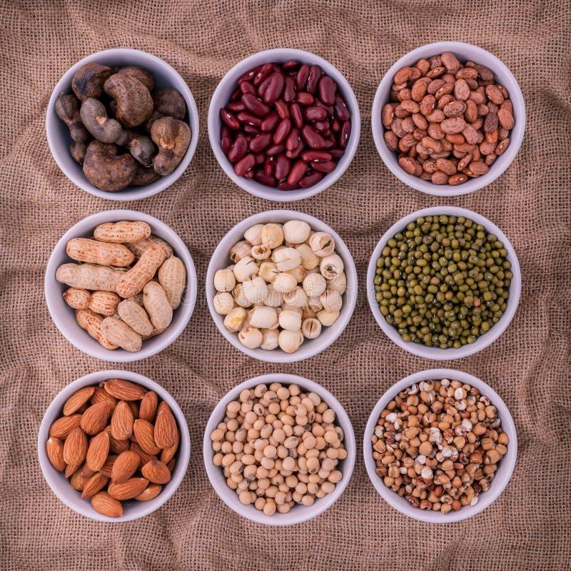混杂的豆、扁豆和坚果在白色碗在棕色布料 免版税库存图片