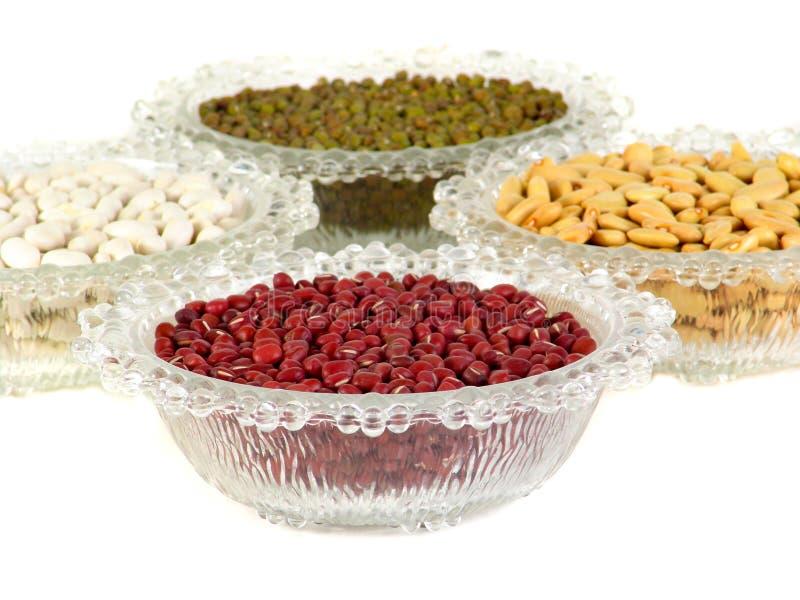 混杂的豆和在白色背景的玻璃碗 绿豆红色扁豆黄豆红豆青豆小米 免版税库存照片