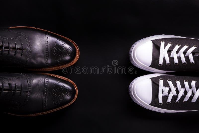 混杂的鞋子 在黑背景的牛津和运动鞋鞋子 人时尚另外样式  比较正式偶然 顶视图 警察 免版税库存图片