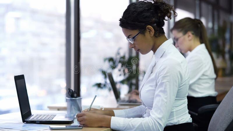 混杂种族做笔记的女商人在纸,勤勉办公室经理 图库摄影