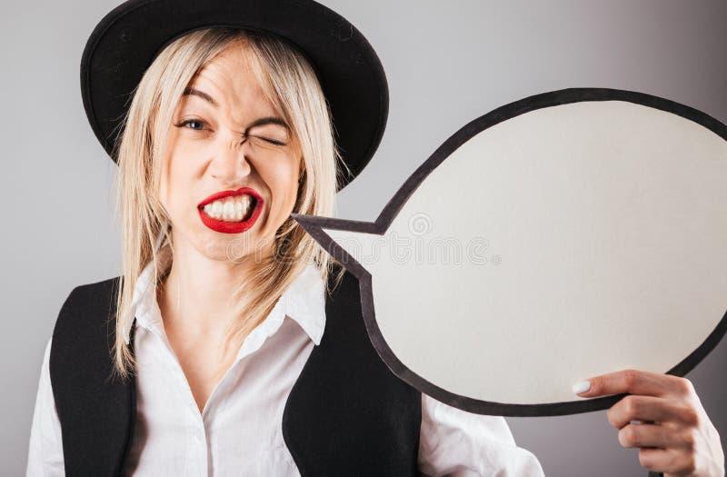 混淆怀疑拿着讲话buble空白的黑帽会议的怀疑妇女和红色嘴唇 库存照片
