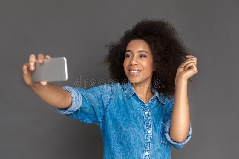E 混血儿在智能手机微笑的灰色采取的selfie隔绝的妇女身分愉快 免版税图库摄影