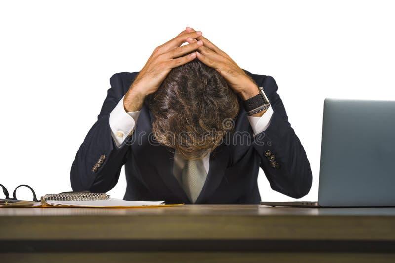 淹没和挫败在便携式计算机办公桌感觉翻倒和被注重的年轻哀伤和沮丧的商人工作 免版税图库摄影
