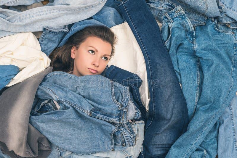 淹没在牛仔裤海洋的女孩  销售概念 黑星期五的概念 库存图片
