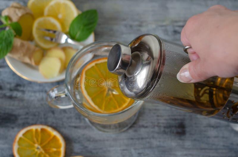 清凉茶用柠檬、姜、贤哲、菩提树和新鲜薄荷叶子 免版税库存照片