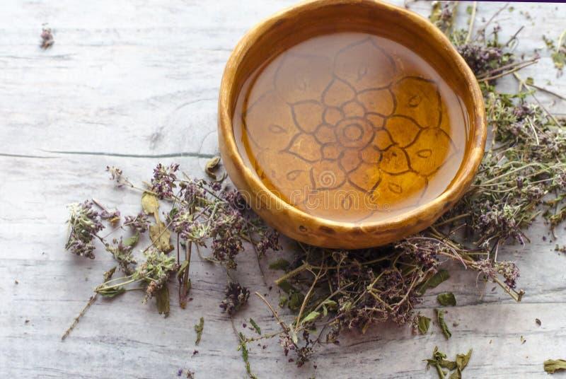 清凉茶用Iwan茶和石南花 陶瓷杯子手工制造与与装饰品坛场的红土 图库摄影