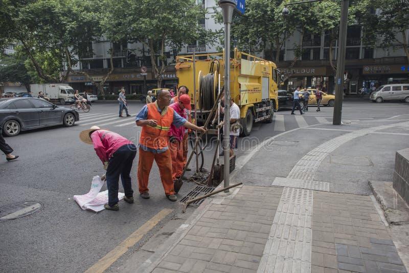 清扫下水道残骸的卫生工作者 库存图片