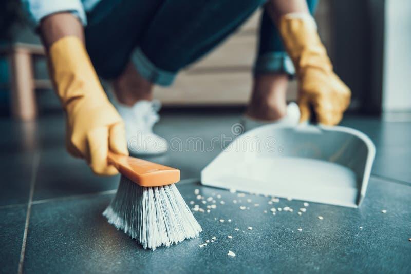清扫与刷子的手套的少妇地板 免版税图库摄影