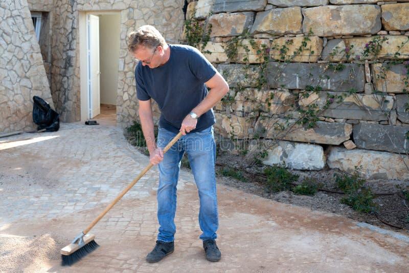 清扫在他推进途中的人石渣 免版税库存图片