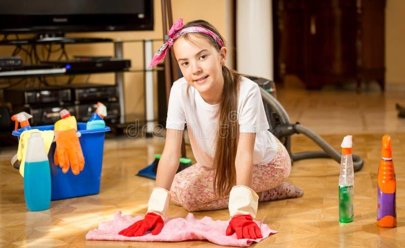 清扫客厅和洗涤木地板的十几岁的女孩 库存图片
