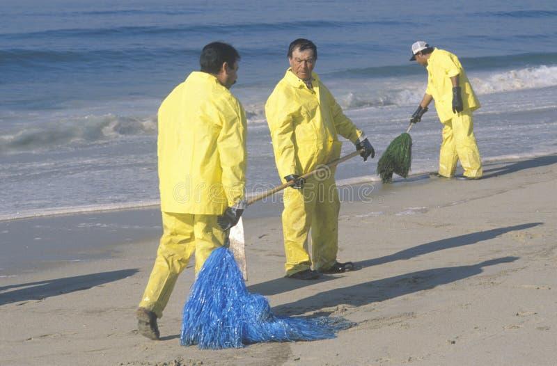 清扫海滩的三名油清洁工作者与吸附性的材料在漏油以后盖了亨廷顿海滩,加利福尼亚 免版税库存图片