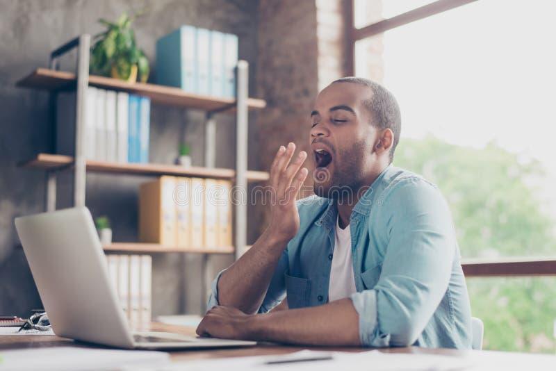 清早在办公室 困疲乏的自由职业者在他的在膝上型计算机` s屏幕前面的工作地点打呵欠桌面的 免版税库存照片