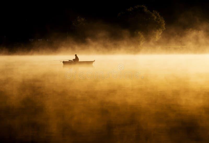 清早日出,在湖的划船一场巨大的雾的 免版税库存图片
