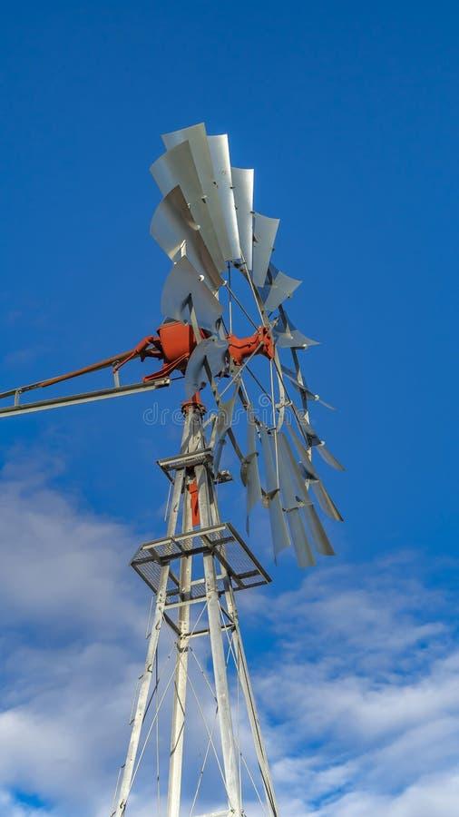 清楚的垂直的关闭与充满活力的天空蔚蓝和松的云彩的一windpump在背景中 免版税库存照片