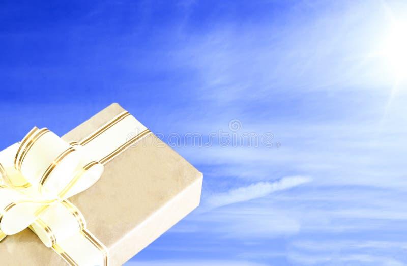 清楚的晴天 天空是蓝色的 在老牌的礼物盒,与金丝带 免版税库存图片