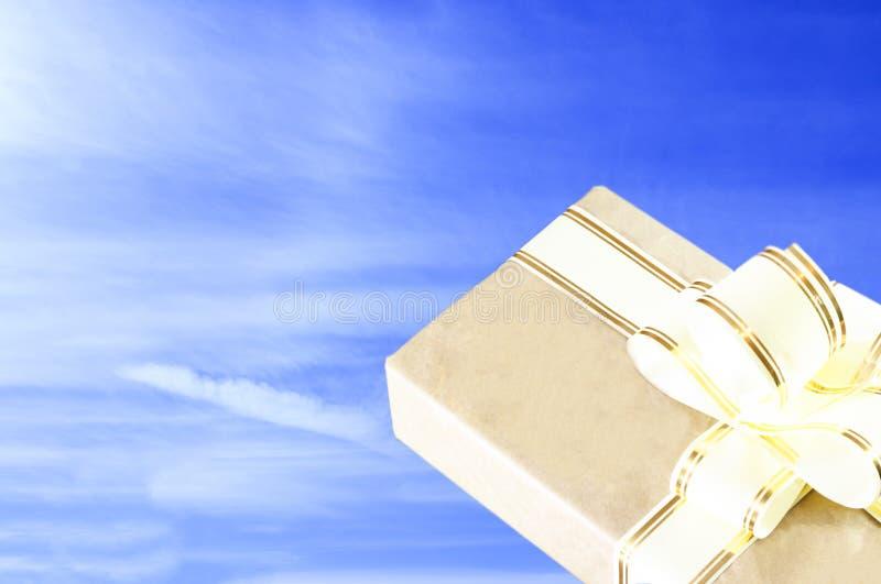 清楚的晴天 天空是蓝色的 在老牌的礼物盒,与金丝带 免版税库存照片