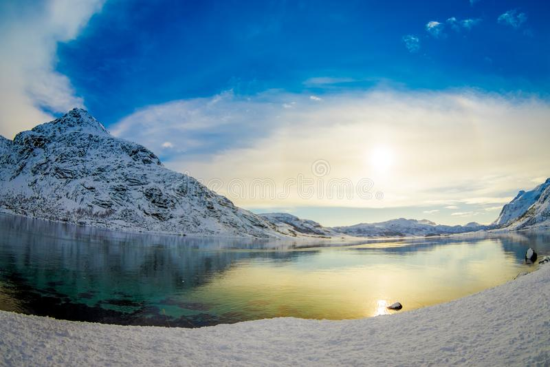 清楚的水华美的室外看法在有反射,当一座巨大的山的太阳的一个湖用雪盖在Lofoten 库存图片