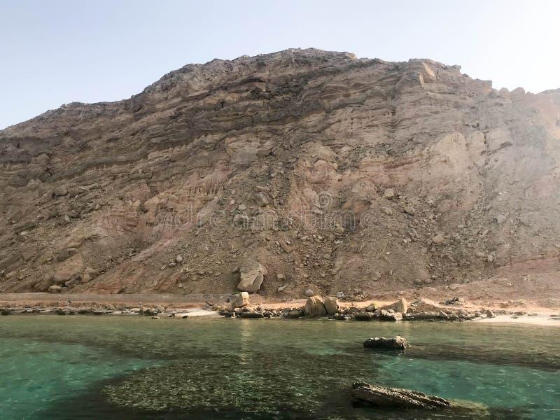 清楚的蓝色自然海盐水,海,有珊瑚礁,以高bro为背景的石头底部的海洋风景  免版税库存照片