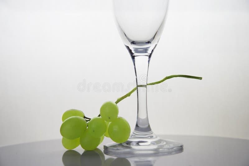 清楚的香槟玻璃用酿酒党的绿色用餐背景的葡萄或食物 库存照片