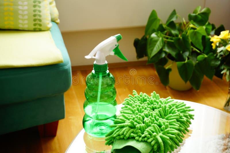 清洁产品、海绵清洗的和洗涤剂在一个绿色瓶在玻璃桌上在客厅,为清洗做准备 免版税库存照片