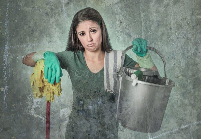 清洁女仆主妇或女仆服务看起来擦净剂的女孩疲乏和沮丧的藏品拖把和洗涤物桶 免版税库存照片