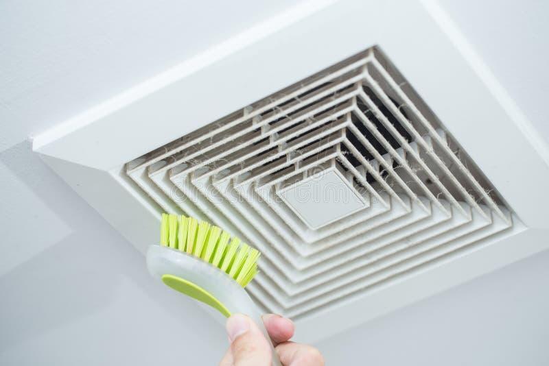 清洁尘土从与刷子的空气管道 免版税库存图片
