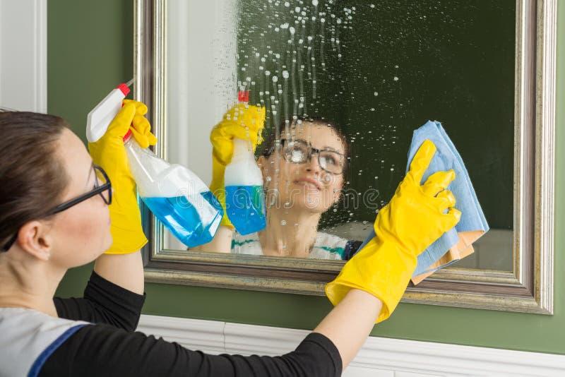 清洁服务 妇女在旅馆清洗镜子 图库摄影