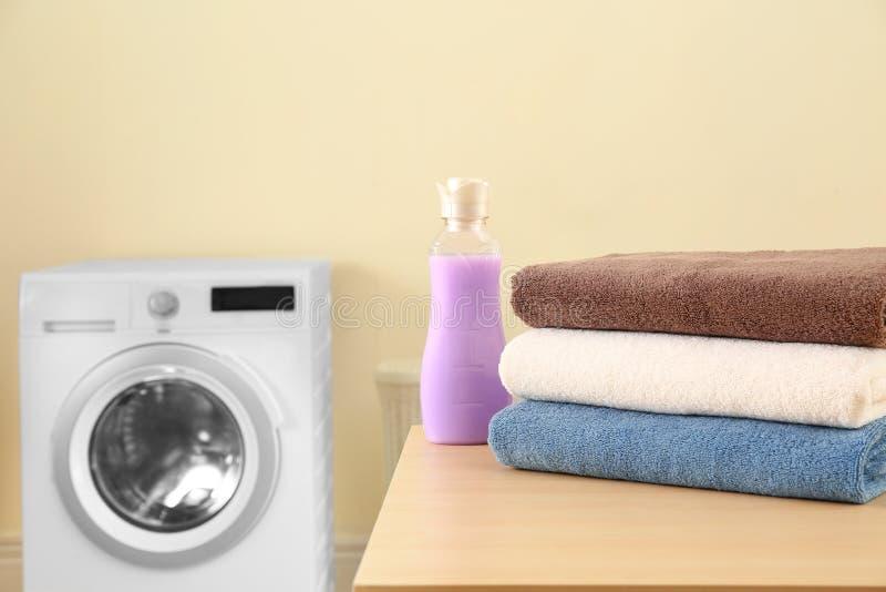 清洁毛巾和瓶在桌上的洗涤剂在洗衣店 r 库存图片