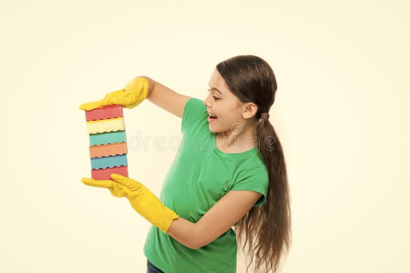 清洁物品 橡胶手套的女孩清洗的拿着许多五颜六色的海绵白色背景 帮助干净  免版税图库摄影