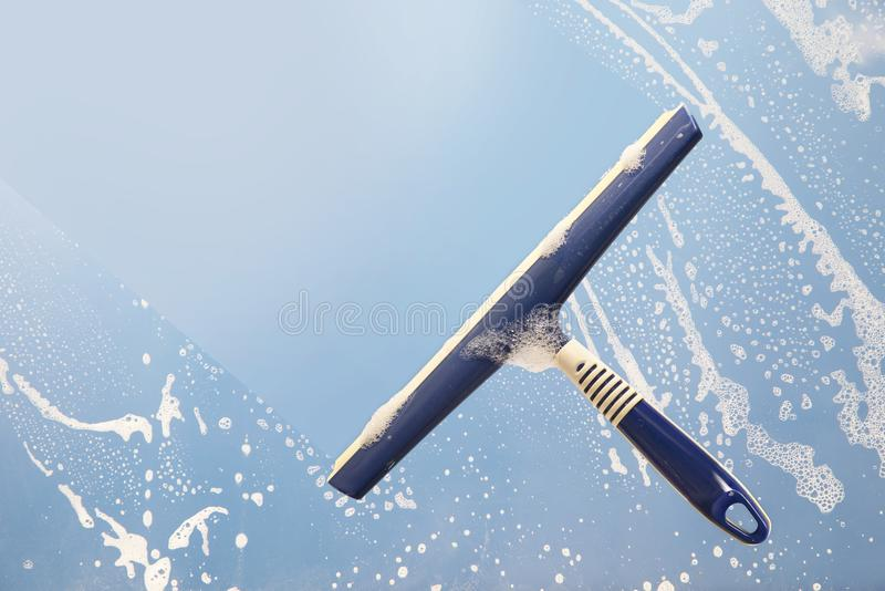 清洗一个肥皂的窗口,春季大扫除的概念的橡皮刮板,蓝色 库存图片