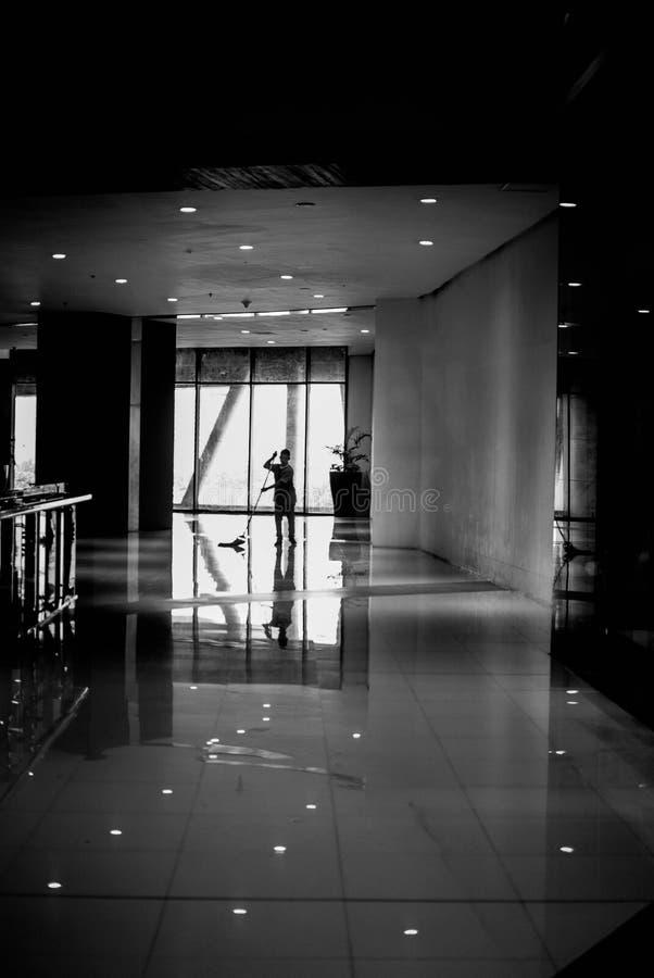 清洗一个购物中心的地板的在黑白的工作者的照片商业目的 免版税库存图片
