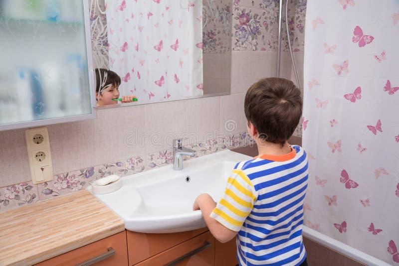 清洗他的牙的年轻男孩在卫生间里与镜子 免版税库存图片
