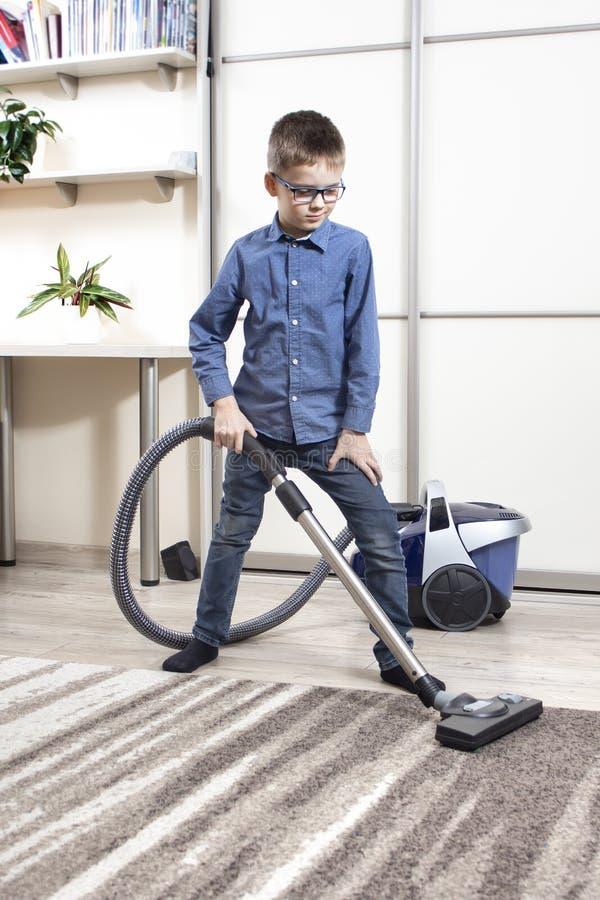 清洗公寓由入学年龄的孩子 儿童的家庭责任 库存照片