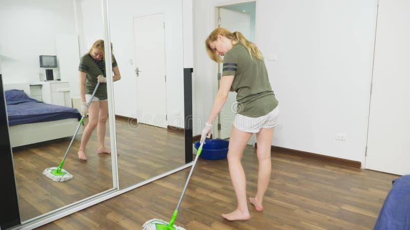 清洗卧室的年轻女人与清洁产品和设备,家事概念 免版税库存照片