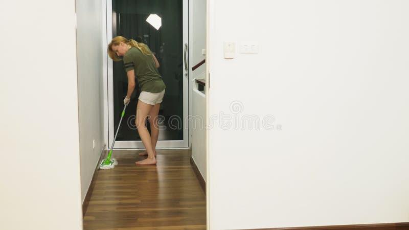 清洗卧室的年轻女人与清洁产品和设备,家事概念 库存照片