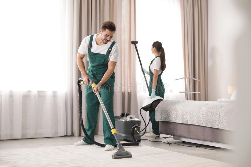 清洗卧室的管理员队与专家 图库摄影