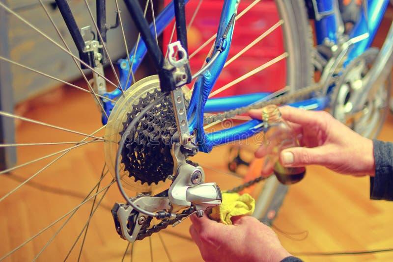 清洗和上油自行车链子和齿轮的男性手特写镜头与油 维护他的新的人自行车 图库摄影