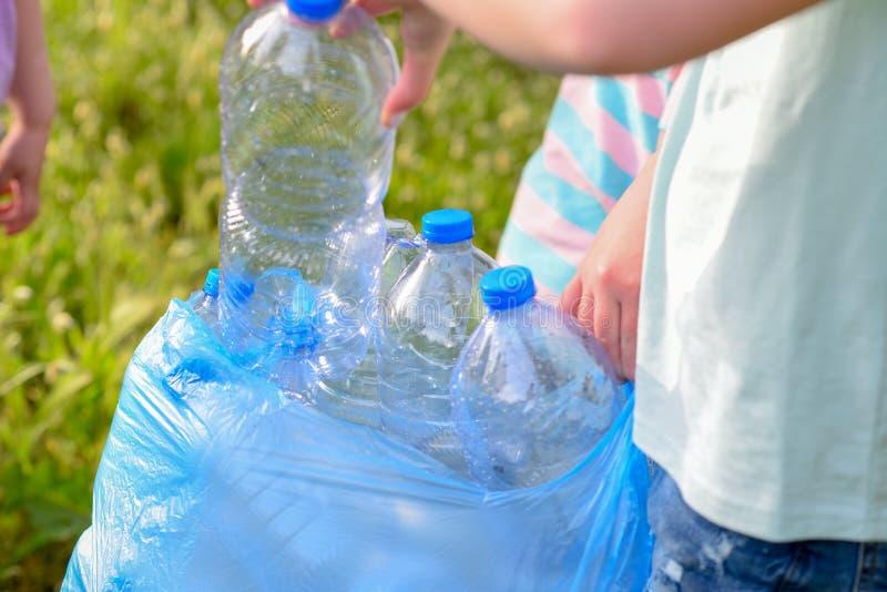 清洗在公园的孩子 有清扫废弃物的垃圾袋的志愿孩子,投入塑料瓶在回收袋子 库存图片